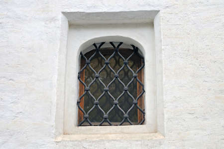 lattice window: Small window of ancient building of white color with a metal lattice