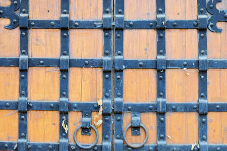 iron hoops: Part of the old wooden gates with handles in the form of rings studded with metal plates Stock Photo