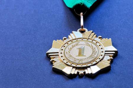 primer lugar: medalla metal del color del oro para el ganador para el primer lugar con una cinta del color verde sobre un fondo azul Foto de archivo
