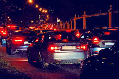 Night traffic jam on a city street: the slow movement of cars with red stop signals.