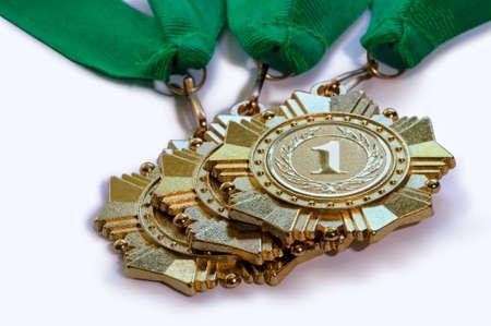 first place: medallas metálicas de color dorado para los ganadores del primer lugar con cintas de color verde se encuentra una sobre otra aislados en un fondo blanco