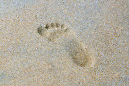 Trace of a bare foot on wet sand.