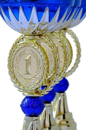 primer lugar: Parte de tazas de metal de adjudicación de color dorado con detalles de color azul para el primer lugar aislado en el fondo blanco Foto de archivo