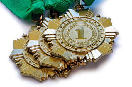 first place: Metal medals of gold color for winners for the first place with ribbons of green color lies one on another isolated on a white background Foto de archivo