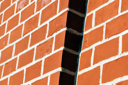 ledge: Red brick wall with white seams. The wall is lit with a sunlight a ledge on a wall in a shadow