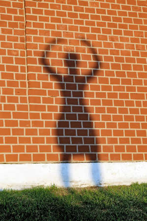 body built: Girls shadow with the raised hands on a red brick wall Stock Photo