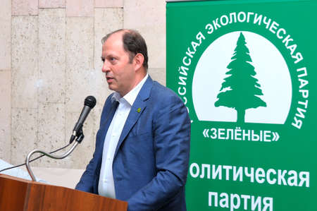 political system: MOSCOW, RUSSIA - JULY 6, 2016: One of the leaders of the Russian Ecological Green Party Oleg Mitvol stands behind the podium against the backdrop of a banner with the logos of the Green Party Editorial