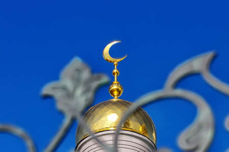 Gold-plated dome of a Muslim mosque with a gilded crescent moon against a blue sky and a decorative fence in the foreground Stock Photo