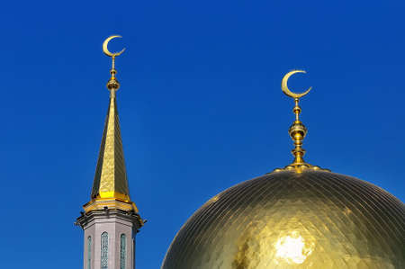 Gilded dome and crescent moon Muslim mosque against the background of the blue sky