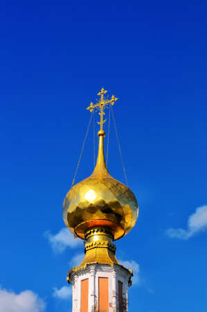 the orthodox church: Gilded dome and cross of Russian Orthodox Church against the background of the blue sky Stock Photo