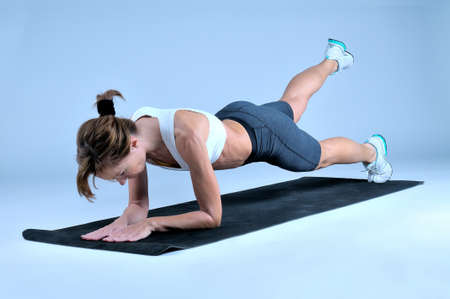 waistline: Sport fitness woman doing exercise on a black gym mat on a gray background. Studio shooting Stock Photo