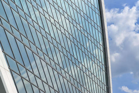 limpid: Wall of modern office building from glass and metal against the blue sky Stock Photo