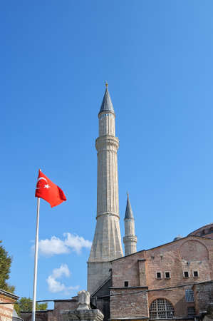 minarets: Minarets of Muslim mosque and Turkish flag against a blue sky