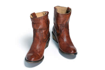 ranch background: Pair of brown leather cowboy boots are isolated on a white background
