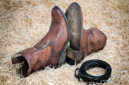 leather belt: Pair of traditional leather cowboy boots and the leather belt curtailed into a ring on straw. Retro toning of the image