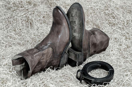 leather belt: Pair of traditional leather cowboy boots and the leather belt curtailed into a ring on straw. Retro and dark toning of the image