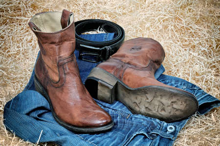 Pair of traditional leather cowboy boots blue jeans and leather belt curtailed into a ring on straw. Retro toning of the image Stock Photo