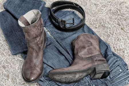 clasp feet: Pair of traditional leather cowboy boots jeans and leather belt curtailed into a ring on straw. Retro and dark toning of the image