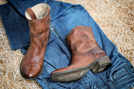 clasp feet: Pair of traditional leather cowboy boots and blue jeans on straw. Retro toning of the image