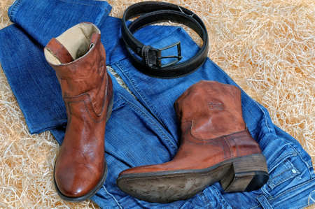 clasp feet: Pair of traditional brown leather cowboy boots and blue jeans and leather brown belt curtailed into a ring on straw