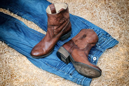 Pair of traditional leather cowboy boots and blue jeans on straw. Retro toning of the image