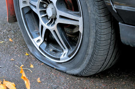Flat tire of a car on the pavement. Side view close up Standard-Bild