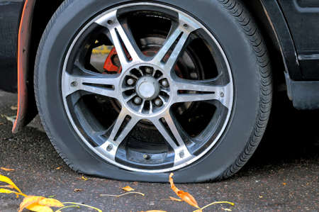 Flat tire of a car on the pavement. Close up