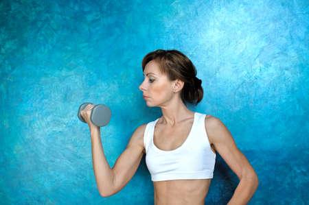 Sport Fitness Frau mit grauen Hanteln in der Nähe einer blauen Wand Übung tut. Studio-Shooting. Lizenzfreie Bilder