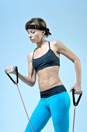 Sport Fitness Frau tun Workout Übung mit Expander auf hellblauen Hintergrund Stretching. Studio-Shooting.