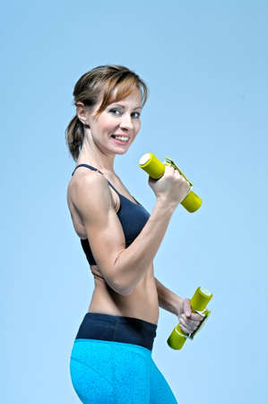 Sport Fitness Frau tun Workout Übung mit gelben Hanteln auf hellblauen Hintergrund in die Kamera. Studio-Shooting. Lizenzfreie Bilder