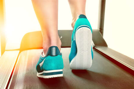 Female legs in turquoise sneakers on a treadmill. Back view.Toned image