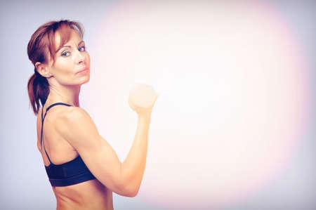 Sport Fitness Frau mit Hanteln tun Übung in die Kamera schaut. Getönten Bild.