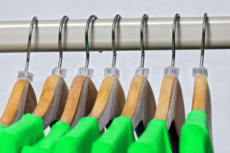 Grüne Damen-T-Shirts hängen auf hölzernen Kleiderbügel mit Indizes der XXS, XS, S, M, L, XL, XXL Größen auf einem grauen Hintergrund.