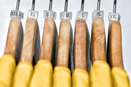 Las camisetas amarillas de las mujeres cuelgan en perchas de madera con índices de los tamaños XXS, XS, S, M, L, XL, XXL en un fondo gris.