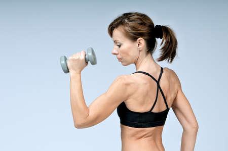 Schöne junge Sportart Fitness Frau mit Hanteln auf einem grauen Hintergrund, der Übung tut. Shooting im Studio.