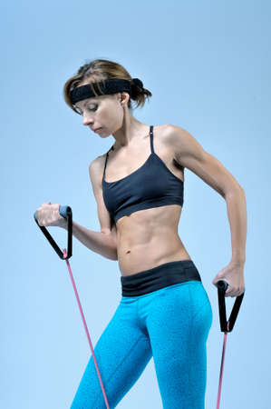 Beautiful young woman in sports wear for fitness doing workout exercise with stretching expander on light-blue background. Studio shoot.