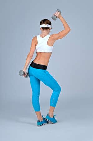 Schöne sexy Sport-Fitness-Frau mit Hanteln tun Workout Übung, während sie mit dem Rücken zur Kamera auf grauem Hintergrund. Shooting im Studio.