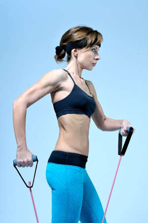 Schöne junge Frau in Sportbekleidung für Fitness mit Stretching Expander auf hellblauen Hintergrund Training Übung. Studio-Shooting.