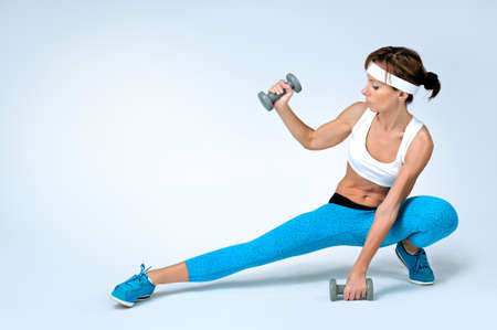 Schöne sexy Sport Fitness Frau tun Workout Übung mit Hanteln grauen Hintergrund. Shooting im Studio.