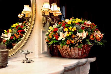 Große Geschenkkorb mit Blumen vor einem dunklen Hintergrund und Reflexion von einem Korb in einem Spiegel Lizenzfreie Bilder