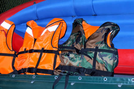 Orange Schwimmwesten und Rettungsweste von Tarnfarbe liegen auf dem rot-blau-Schlauchboot Lizenzfreie Bilder