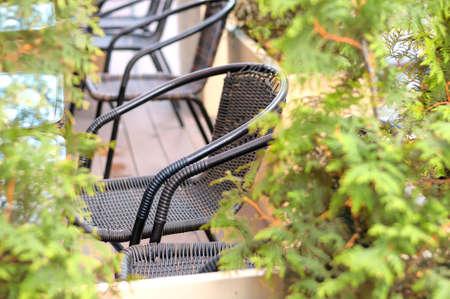 Wicker garden chairs surrounded by green plants. Selective focus. Shallow depth of field. Toned image Lizenzfreie Bilder