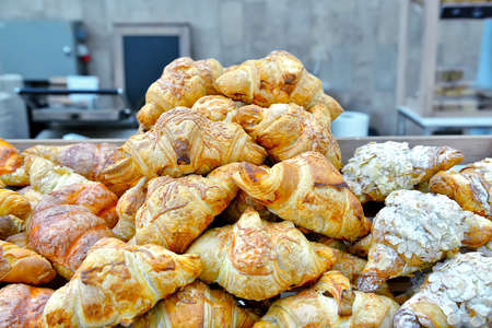selectively: Hill of fresh croissants on the bakery equipment background. Selectively tinted image