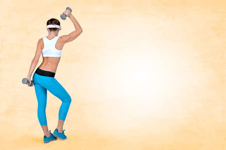 Beautiful sexy sport fitness woman doing workout exercise with dumbbells while standing with her back to the camera on peach background. Shooting in studio.