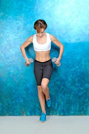 Sport Mädchen in der Abnutzung für die Fitness und das türkisfarbene Turnschuhe steht in der Nähe einer blauen Wand und hält grau Hanteln in den Händen. Studio-Shooting.