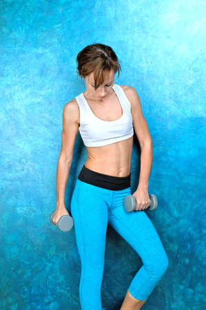 Sport girl in wear for fitness stands near a blue wall and holds gray dumbbells in hands. Studio shoot.