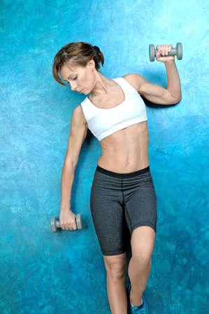 Sport Mädchen in der Abnutzung für Fitness steht in der Nähe einer blauen Wand und hält grau Hanteln in den Händen. Studio-Shooting.