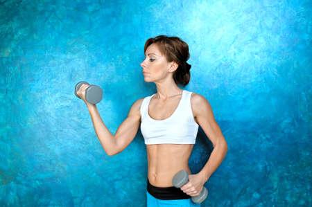 Sport Mädchen in der Abnutzung für Fitness in der Nähe einer blauen Wand und hält grau Hanteln in den Händen. Studio-Shooting.