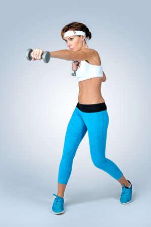 Schöne sexy Sport-Fitness-Frau in Weiß und Türkis Sport türkis Turnschuhe Training Übung mit Hanteln vor grauem Hintergrund zu tun. Shooting im Studio.