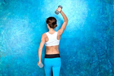 Sport Mädchen in der Abnutzung für die Fitness tun Workout Übung mit Hanteln, während sie mit dem Rücken zur Kamera gegen den blauen Wand. Shooting im Studio. Lizenzfreie Bilder